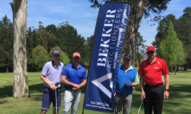 Four golfers standing in front of banner