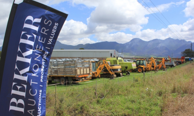 Banner in foreground with machinery and implements in background